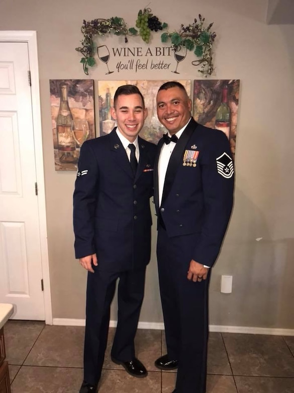 U.S. Air Force Airman 1st Class Anthony Castro and Master Sgt. Jonathan Herrera pose for a photo before Herrera's SNCO Induction Ceremony at Davis-Monthan Air Force Base, Ariz., Aug. 31, 2018. Herrera and Castro are a father and son duo both in the Air Force, assigned to the same Air Force Specialty Code, same duty station at Davis-Monthan Air Force Base, Ariz., and now the same deployed location at Al Dhafra Air Base, United Arab Emirates. (Courtesy photo)