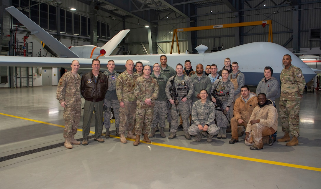 Members of U.S. Air Force 52nd Operations Group, Detachment 2, Col. Jason Bailey, 52nd Fighter Wing commander, far left, and Chief Master Sgt. Alvin Dyer, 52nd FW command chief, far right, pose for a photograph in front of a General Atomics MQ-9 Reaper remotely piloted aircraft at Miroslawiec Military Air Base, Poland, Jan. 29, 2019. Det. 2 is home to about 75 military and contractor personnel. (U.S. Air Force photo by Airman 1st Class Kyle Cope)