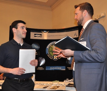 """IMAGE: FREDERICKSBURG, Va. (Feb. 5, 2019) - A Naval Surface Warfare Center Dahlgren Division (NSWCDD) representative discusses career opportunities with a candidate at the NSWCDD Career Fair. The command made 36 on-the-spot job offers at the event held in the Fredericksburg Expo and Conference Center. """"This is the first year that we opened the event up to non-science and engineering positions and we had an overwhelming response for our contract, financial, and information technology positions,"""" said Shelby Khan, the NSWCDD Human Resources Recruiting Program lead. """"We anticipate additional interviews and offers resulting from the career fair in the weeks to come."""""""