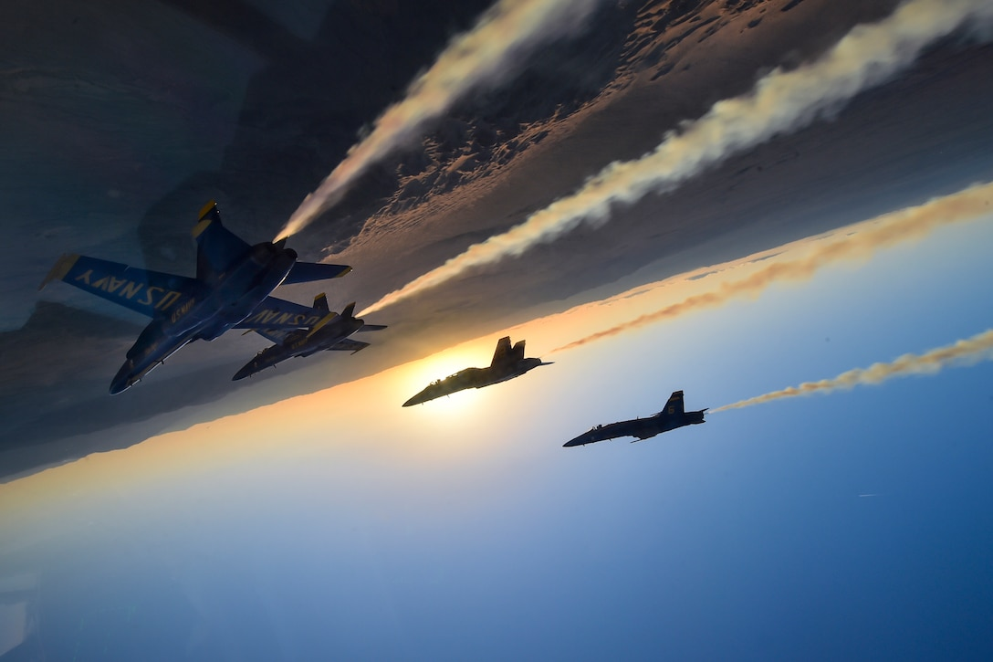 Military jets perform an acrobatic maneuver in a twilight sky.
