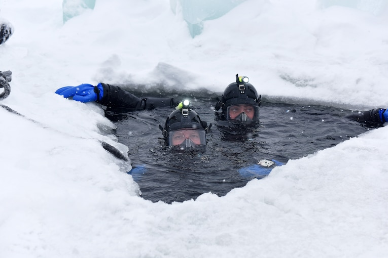 Two divers peak through a hole in the ice.