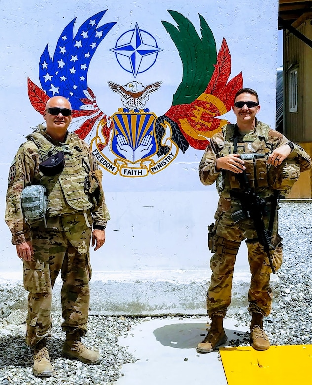 U.S. Air Force Lt. Col. John Shipman, Train, Advise, Assist Command-Air chaplain and Staff Sgt. Tony Hanks, 307th Bomb Wing religious affairs specialist stand by a mural at Hamid Karzai International Airport in Kabul, Afghanistan, July 12, 2018. Hanks was responsible for the safety of Shipman during their deployment. Chaplains are non-combatants and do not carry weapons.  (Courtesy photo)