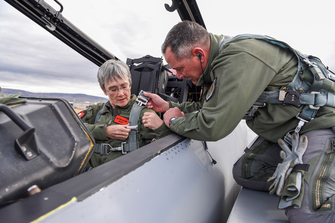 Air Force Col. Jeff Smith, 173rd Fighter Wing commander, helps Air Force Secretary Heather Wilson strap into an F-15D Eagle before a familiarization flight at Kingsley Field in Klamath Falls, Ore.