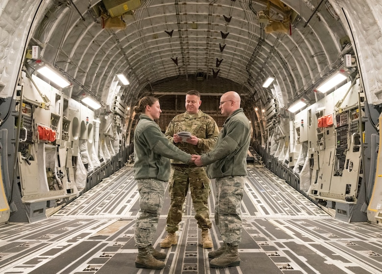 U.S. Air Force Tech. Sgt. Joseph Rice, 436th Aerial Port Squadron ramp operations supervisor, officiates a wedding ceremony for U.S. Airmen in the cargo compartment of a C-17 Globemaster III Jan. 29, 2018, at Dover Air Force Base, Delaware. Rice has been ordained for 10 years, but this was the first wedding he had ever officiated aboard an aircraft. (U.S. Air Force photo by Roland Balik)