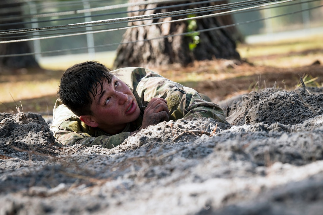 Senior Airman Shawn King, 823d Base Defense Squadron fireteam member, low crawls through an obstacle during an Army Air Assault Assessment (AAA), Jan. 20, 2019, at Camp Blanding, Fla. The AAA is designed to determine Airmen's physical and mental readiness before being selected to attend Army Air Assault school. (U.S. Air Force photo by Airman First Class Eugene Oliver)