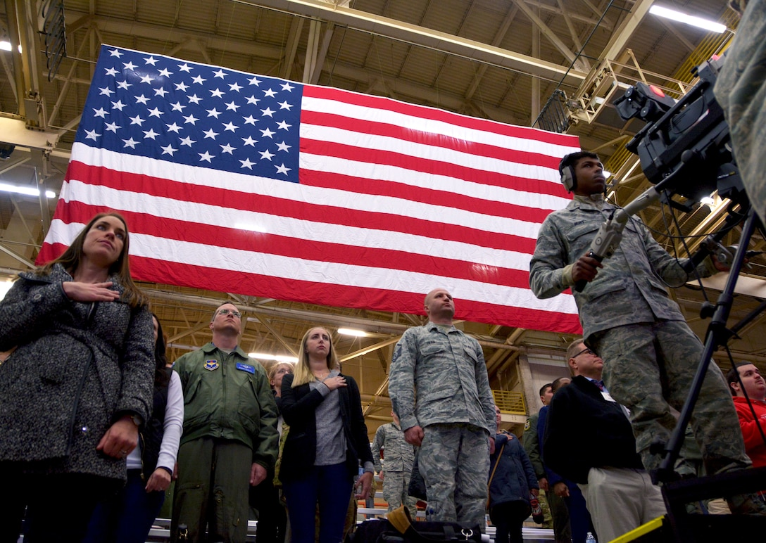 Guests of the KC-46A Pegasus arrival celebration stand during the national anthem at Altus Air Force Base, Oklahoma, Feb. 8, 2019. The KC‐46A provides improved capabilities over older Air Force air refueling aircraft to include boom and drogue refueling on the same sortie, a refueling capability of more than 212,000 pounds of fuel and palletized cargo up to 65,000 pounds, depending on fuel storage configuration. (U.S. Air Force photo by Tech. Sgt. Samantha Mathison)