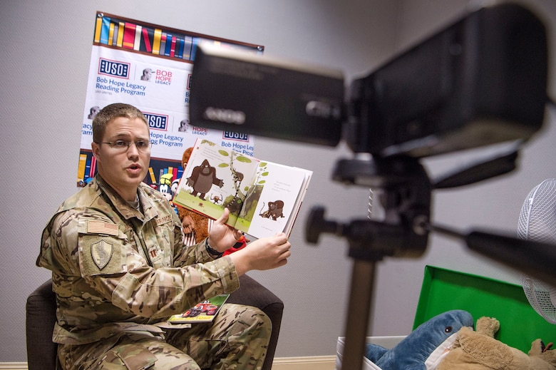 U.S. Air Force Capt. Nathan Badger, 34th Intelligence Squadron flight commander, records himself reading a book as part of United Service Organizations (USO) Qatar's reading program Feb. 8, 2019, at Al Udeid Air Base, Qatar. The USO reading program allows service members to record themselves reading books to send back to their children. Program participants can write messages in the books and send them to their children along with the video recording. (U.S. Air Force photo by Tech. Sgt. Christopher Hubenthal)