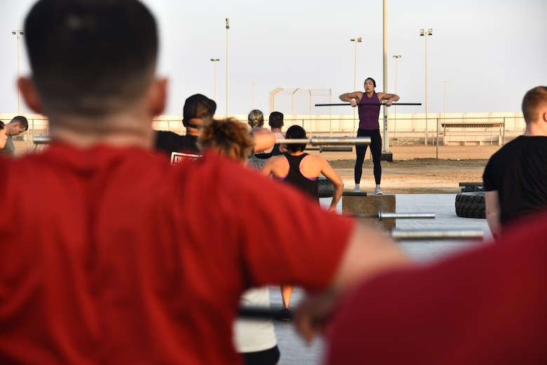 Stephanie Chung, professional CrossFit athlete, demonstrates basic CrossFit techniques during a meet-and-greet event at Al Dhafra Air Base, United Arab Emirates, Dec. 21, 2018. The 380th Expeditionary Force Support Squadron Fitness Center Staff coordinates meet-and-greets with professional athletes. (U.S. Air Force photo by Senior Airman Mya M. Crosby)