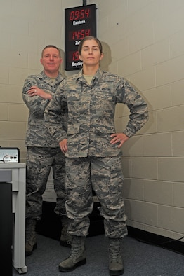 Two military members stand in a room with a clock