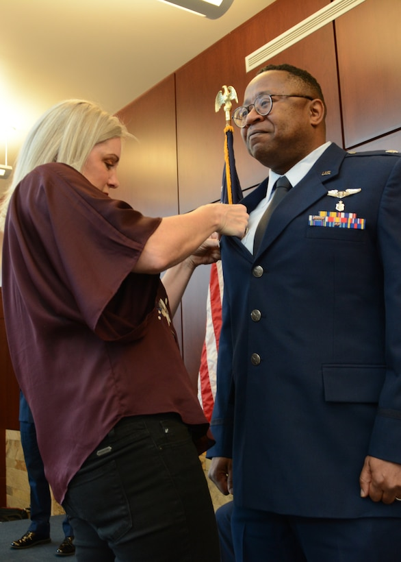 Lt. Col. (Dr.) Alvin Bradford's wife, Dina, attaches the commanders pin onto Bradford's service coat for the first time during the 507th Medical Squadron assumption of command ceremony at Tinker Air Force Base, Oklahoma, Feb. 9, 2019. Prior to assuming command, Bradford served as the Chief of Aerospace Medicine in the 507th MDS. (U.S. Air Force photo by Master Sgt. Grady Epperly)