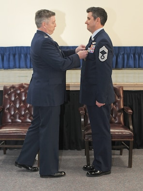 Two figures in profile, Col. reaching across to pin medal on Chief Master Sgt. against a curtain backdrop.