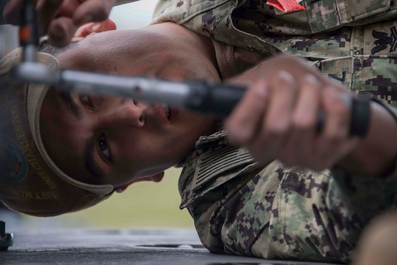 U.S. Navy Petty Officer 2nd Class Sergio Valasquez, a mineman with Navy Munitions Command Atlantic Unit Charleston tightens a bolt on an inert underwater mine at Barksdale Air Force Base, Louisiana, Jan. 30, 2019.  The mines are prepared by Navy personnel, but loaded onto a B-52 Stratofortress by Reserve Citizen Airmen.  The B-52 can lay mines as part of its maritime capabilities. (U.S. Air Force photo by Master Sgt. Ted Daigle)