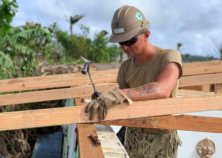 TINIAN, Northern Mariana Islands --- Builder 3rd Class Matthew Winnett, assigned to Naval Mobile Construction Battalion 3, Det. Tinian, nails in a truss, Jan. 25, for a temporary emergency roof for a home that was damaged during Super Typhoon Yutu.