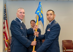 Col. Roger R. Stoeckmann, commander of the 459th Mission Support Group, passes the guidon to Maj. Billy J. Ancheta, commander of the 459th Force Support Squadron, during an assumption of command ceremony at Joint Base Andrews, Maryland, Feb. 9, 2019. Ancheta's previous assignment was with the Force Visibility Branch for the Generation Center where he served as the chief. (Photo by U.S. Air Force Senior Airman Andreaa Phillips)