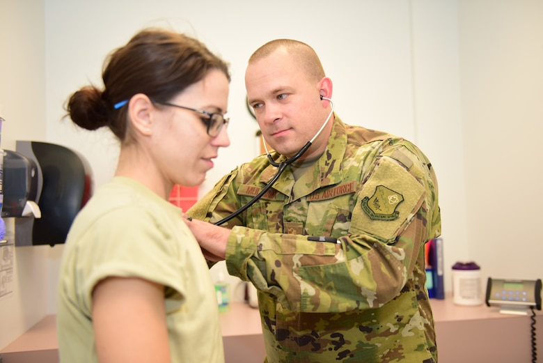Maj. Matthew Mullinix (right), a physicians' assistant with the 193rd Special Operations Medical Group, examines a patient as part of a routine check-up during a unit training assembly Nov. 18, 2018, at the 193rd Special Operations Wing, Middletown, Pennsylvania. Recently, while on temporary duty in Lithuania, Mullinix helped to save the life of a civilian by administering cardiopulmonary resuscitation. (U.S. Air National Guard photo by Tech. Sgt. Claire Behney/Released)