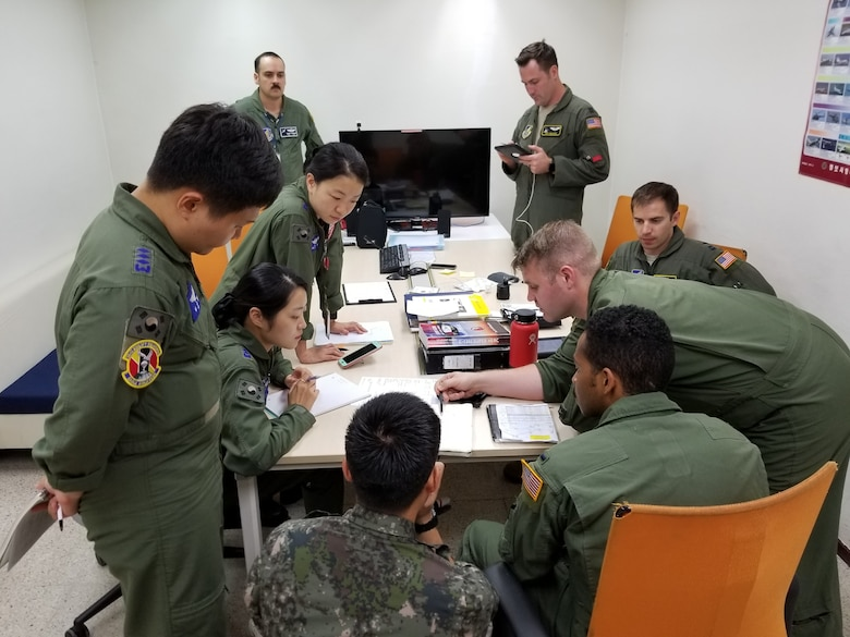 U.S. Airmen assigned to the 36th Tactical Airlift Squadron from Yokota Air Base, Japan, and Republic of Korea airmen assigned to the 251st Airlift Squadron conduct mission planning at Gimhae Air Base, July 2018. (Courtesy photo by Captain Jason Lim)