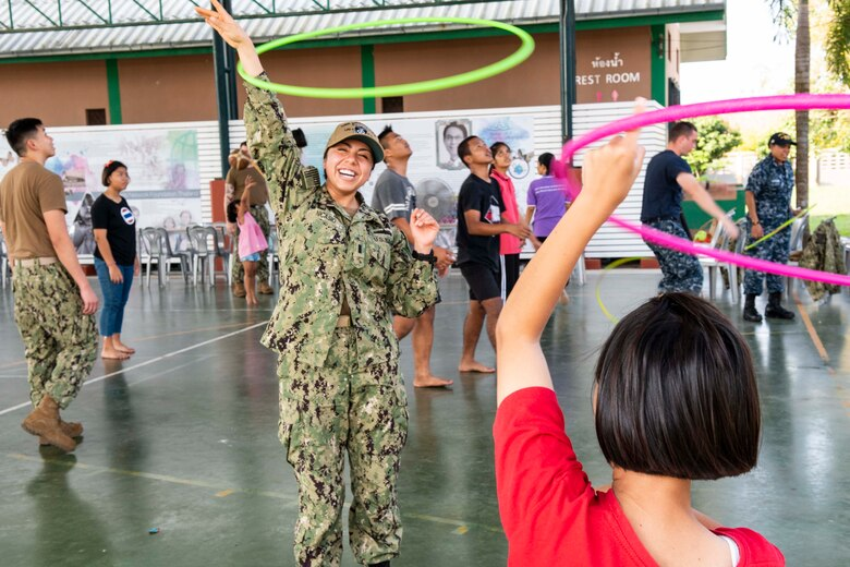 190209-N-DX072-1072 CHONBURI, Thailand (Feb. 9, 2019) – Lt. j.g. Jasmin Nicasio, from San Diego, hula hoops with a child during a community service project at the Child Protection and Development Center in Chonburi, Thailand. The amphibious transport dock ship USS Green Bay (LPD 20), part of the Wasp Amphibious Ready Group, with embarked 31st Marine Expeditionary Unit (MEU), is in Thailand to participate in Exercise Cobra Gold 2019. Cobra Gold is a multinational exercise co-sponsored by Thailand and the United States that is designed to advance regional security and effective response to crisis contingencies through a robust multinational force to address common goals and security commitments in the Indo-Pacific region.