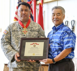 Gov. David Ige presents State Medal of Valor recipient, Staff Sgt. Gregory A.Y. Lum Ho, Jr., with award certificate during  a ceremony held on Feb. 9, 2019, at Wheeler Army Airfield, Hawaii. Lum Ho was awarded the State Medal of Valor for ignoring substantial risk to his own life to ensure the rescue of a family of six while supporting Hawaii National Guard response efforts to Tropical Storm Lane on Aug. 23, 2018,