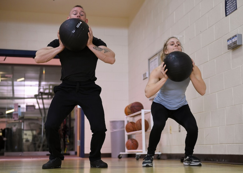 U.S. Air Force Senior Airman Tyler, 30th Intelligence Squadron, and Elise Lang, daughter of retired U.S. Air Force Lt. Col. Kenneth Lang, throw medicine balls at Joint Base Langley-Eustis, Virginia, Feb. 7, 2019.
