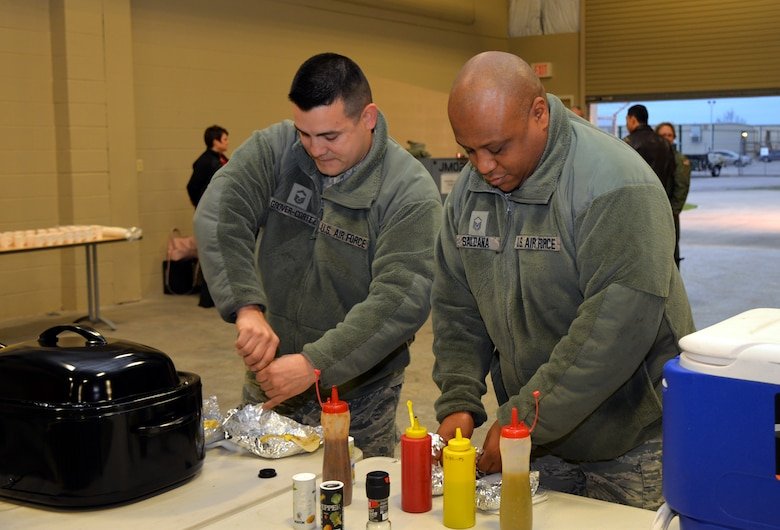 Senior Master Sgt. Dallas Grover-Cortez, 433rd Maintenance Squadron hydraulics section chief, and Master Sgt. Michael Saldana, 433rd MXS hydraulic maintenance, season their tacos at the C-5 Rodeo Round-Up Breakfast Feb. 8, 2019 at Joint Base San Antonio-Lackland.