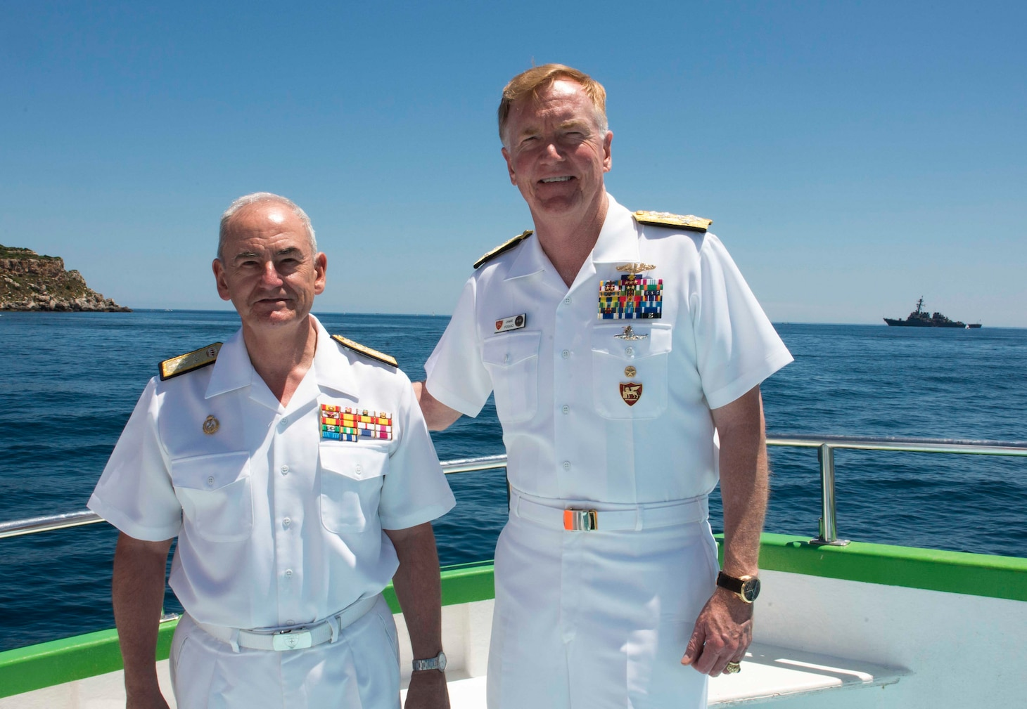 Adm. James G. Foggo III, commander, U.S. Naval Forces Europe-Africa and commander, Allied Joint Force Command Naples, Italy, right, and the Chief of Staff of the Spanish navy Adm. Gen. López Calderón pose for a photo with USS Donald Cook (DDG 75) in the background before a commemoration ceremony honoring the 150-year legacy of Adm. David Farragut in Minorca, Spain, June 16, 2018.
