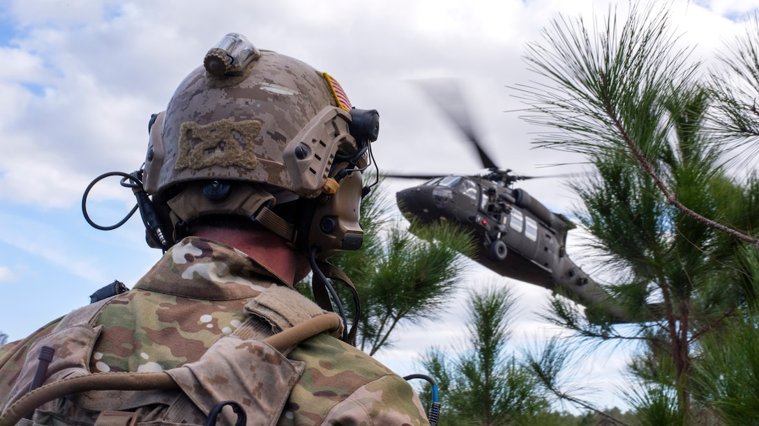 A U.S. Navy Sea, Air and Land (SEAL) team member awaits extraction from a UH-60 Black Hawk helicopter during an Emerald Warrior 2019 search and rescue training exercise, Jan. 22, 2019.