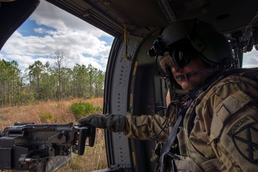 A U.S. Army 2-10 Assault Helicopter Battalion UH-60 Black Hawk gunner from Fort Drum, N.Y., provides aerial support during an Emerald Warrior combat search and rescue scenario, Avon Park, Florida, Jan. 22, 2019.