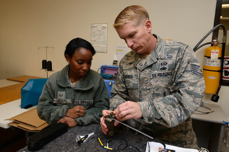 Tech. Sgt. Brandon Dutreix, 403rd Operations Support Squadron aircrew flight equipment craftsman, instructs Senior Airman Tabitha Williams, 403rd OSS aircrew flight equipment journeyman, on how to assemble and inspect an AN/URT-44 personnel locator beacon January 10, 2015. The Air Force Life Cycle Management Center's Agile Combat Support Directorate is currently fielding 12,000 new personnel locator beacons to replace the URT-44(U.S. Air Force photo/Tech. Sgt. Ryan Labadens)
