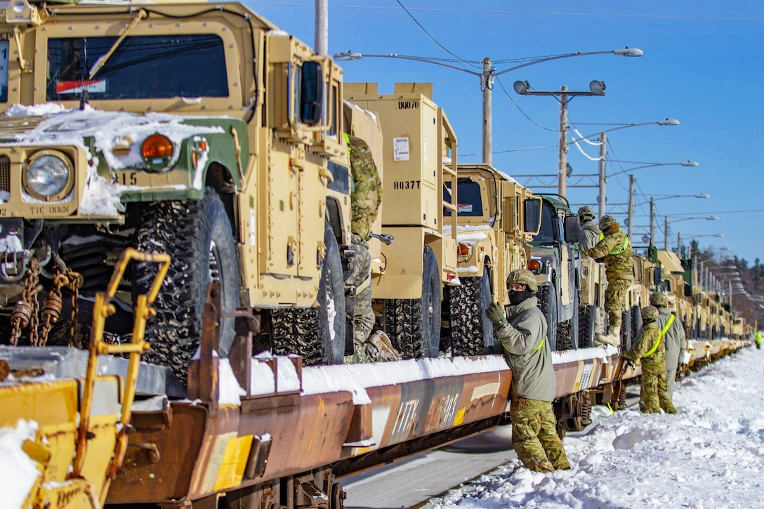 Soldiers standing in snow secure military vehicles on a railway.