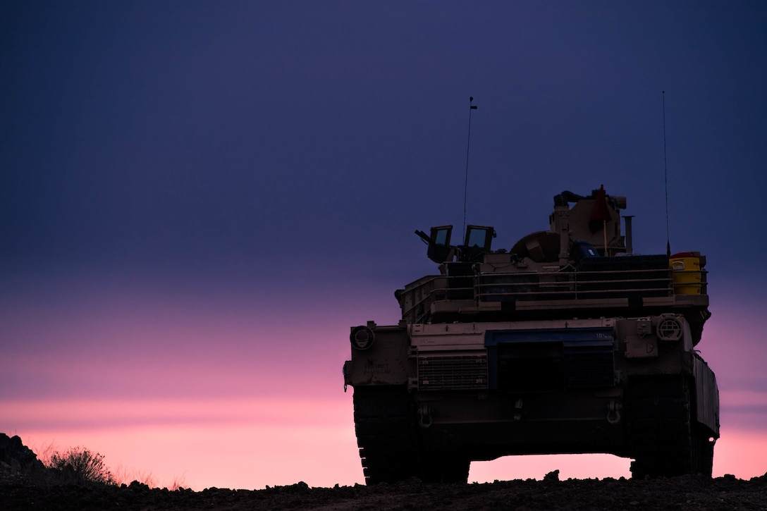 A tank parked at sunset.