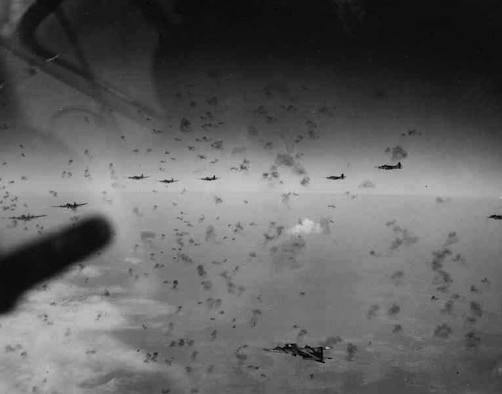 B-17 formation under attack during a bombing raid on an industrial target in Germany, probably sometime in 1943. By fall 1943, German antiaircraft defenses—fighters, ground-based anti-aircraft artillery batteries and specially designed flak towers around key industrial centers—had become quite formidable. The black smoke dots came from exploding AAA shells, fitted with proximity fuses. (U.S. Air Force photo)