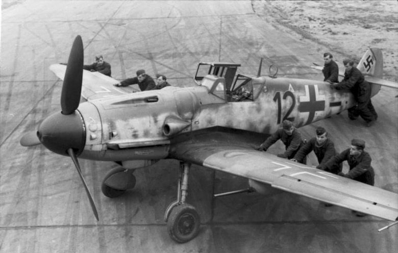 Luftwaffe ground crew positioning a Messerschmitt Bf 109G-6 equipped with an underwing gondola cannon kit, assigned to a Luftwaffe squadron in France, late 1943. The cannon was especially effective in attacking American strategic bombers. This aircraft was one of several types of German fighters that engaged B-17 bombers and P-51 fighters during Operation Argument. (Archive photo)