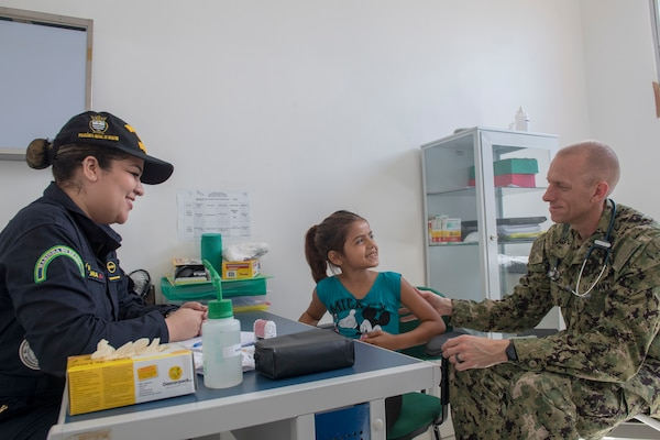 Brazilian Navy 1st Lt. Livia Laura, left, and Cmdr. Edmund Milder, right, examine a young patient during a visit to the Heraclio Emiliano Moda medical clinic in Axinim, Brazil, Feb. 6.