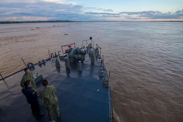 Lt. John Sullivan, Brazilian Navy Capt. Hilcelio Freitas, and Lt. Cmdr. Robert Lennon converse as the Oswaldo Cruz-class hospital ship NAsH Carlos Chagas (U19) enters the Amazon River to commence a month-long humanitarian mission, Feb. 4.