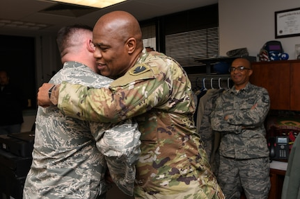 Chief Master Sgt. Anthony Potts, right, Oklahoma Air National Guard state command chief, Oklahoma Joint Force Headquarters, hugs Master Sgt. Scott Crim, a 137th Special Operations Logistics Readiness Squadron (137th SOLRS) heavy equipment mechanic, during an informal coining in Crim's office at Will Rogers Air National Guard Base in Oklahoma City, Feb. 5, 2019.