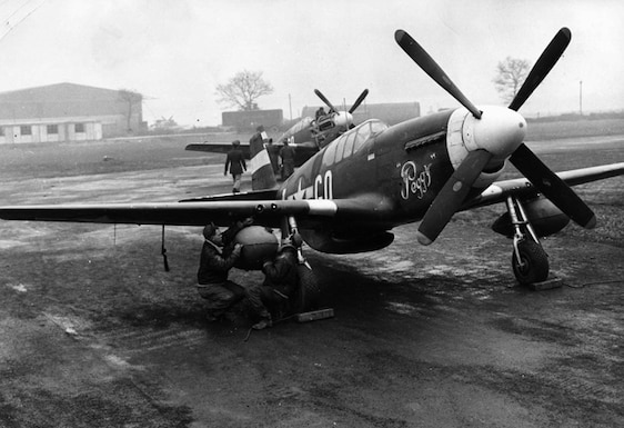 Two P-51D Mustangs at an English airfield in early 1944. The ground crew is fitting the second of two underwing fuel tanks, which allowed the Mustangs to escort American strategic bombers to their targets inside Germany, engage German fighters and return to their bases in England. (U.S. Air Force photo)