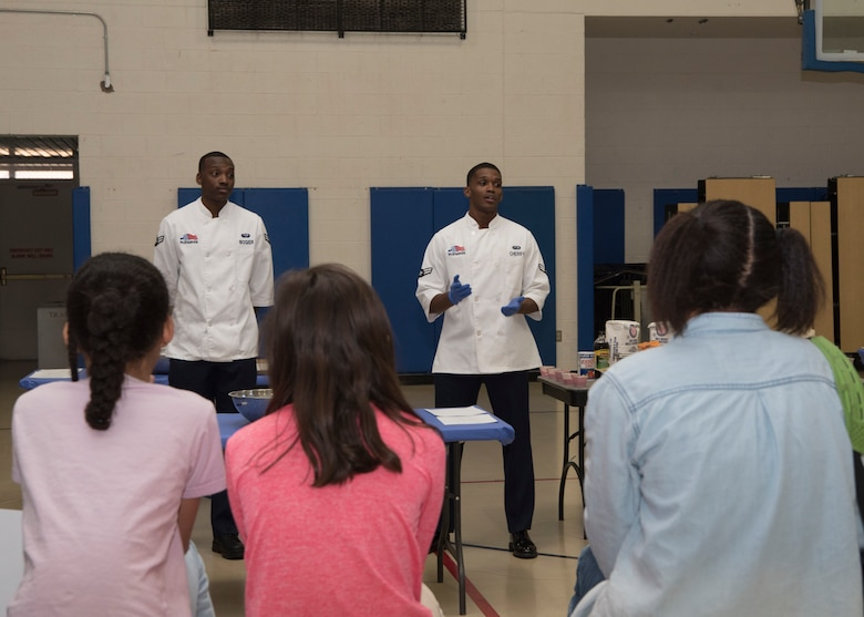 (From left to right) Airman 1st Class Dominick Bogier, 49th Force Support Squadron food service apprentice and Airman 1st Class Malik Cherry, 49th FSS food service specialist, brief youth baking competition teams on the challenge, Jan. 30, 2019, on Holloman Air Force Base, N.M. Five teams from the Youth and Teen Center participated in a cookie baking challenge to win golden spatulas. (U.S. Air Force photo by Airman Autumn Vogt)