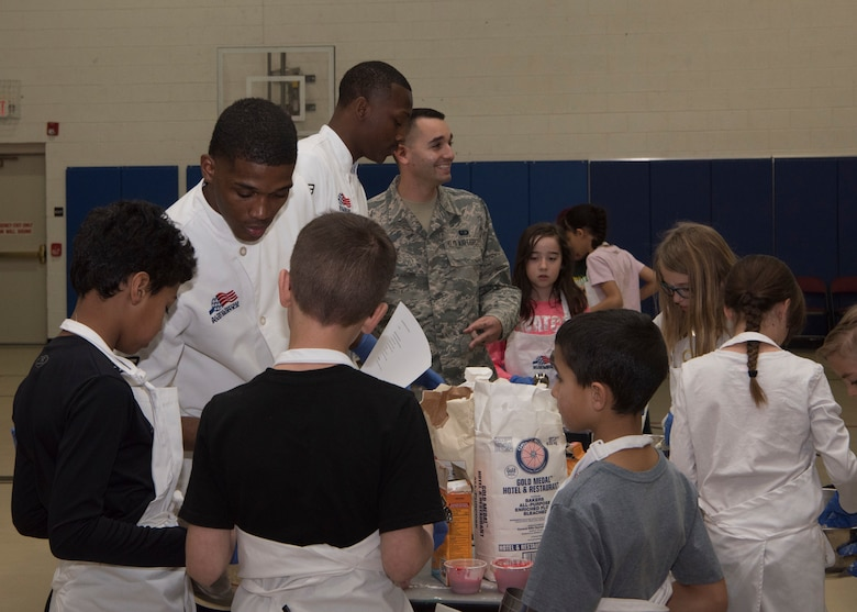 (From left to right) Airman 1st Class Malik Cherry, 49th Force Support Squadron food service specialist, and Airman 1st Class Dominick Bogier, 49th FSS food service apprentice, assist youth baking competition teams with gathering cookie ingredients, Jan. 30, 2019, on Holloman Air Force Base, N.M. Seventeen members of the Youth and Teen Center signed up for a cookie baking competition and the competition lasted two and a half hours. (U.S. Air Force photo by Airman Autumn Vogt)