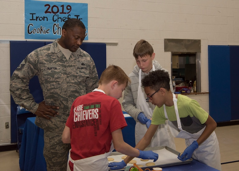 Chief Master Sgt. Bobby Drayton, 49th Force Support Squadron superintendent, watches team Papyrus' Cookie Corner place sugar cookies on a baking sheet, Jan. 30, 2019, on Holloman Air Force Base, N.M. Seventeen members of the Youth and Teen Center signed up for a cookie baking competition and the competition lasted two and a half hours. (U.S. Air Force photo by Airman Autumn Vogt)