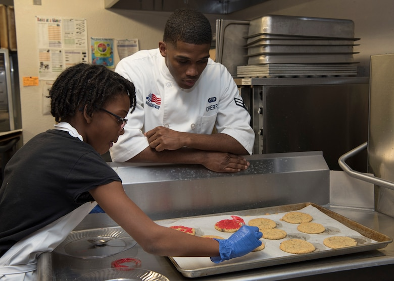 (From left to right) Ysabelle Smith, This is Sparta team leader (left), receives advice on making frosting hearts for cookies from Airman 1st Class Malik Cherry, 49th FSS food service specialist (right), Jan. 30, 2019, on Holloman Air Force Base, N.M. Seventeen members of the Youth and Teen Center signed up for a cookie baking competition and the competition lasted two and a half hours. (U.S. Air Force photo by Airman Autumn Vogt)