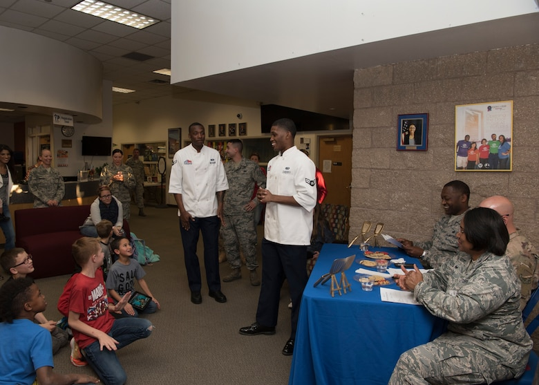 Youth gather as Airman 1st Class Malik Cherry, 49th Force Support Squadron food service specialist (middle), announces who won the baking competition, Jan. 30, 2019, on Holloman Air Force Base, N.M. Out of the five teams from the Youth and Teen Center competing in cookie baking, Papyrus's Cookie Corner, was announced as the winner and received golden spatulas. (U.S. Air Force photo by Airman Autumn Vogt)