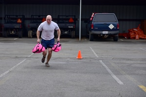 A man wearing the Air Force physical training uniform runs with 2 pink sandbags.
