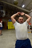 A man wearing the Air Force physical training gear throws a medicine ball.
