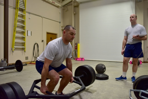 A man wearing the Air Force phyisical training gear does a deadlift.