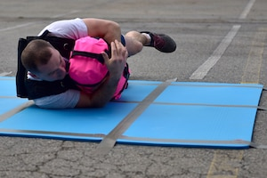 A man rolls with a pink sandbag and a weighted vest.