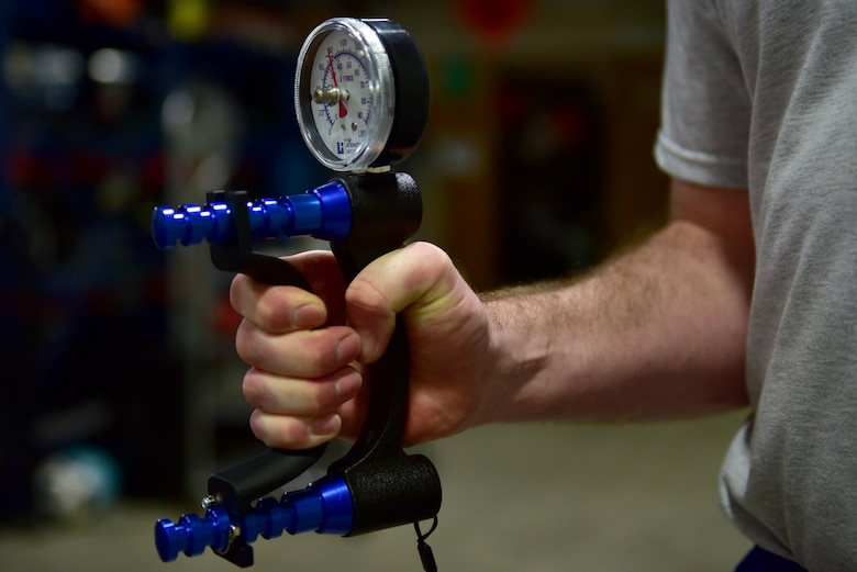 A hand squeezes a device that measures how strong someone's grip strength is.
