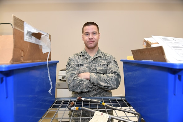 An Airman poses for a photo with his arms crossed