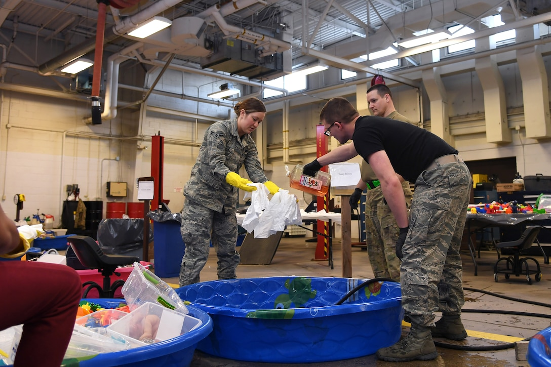 Airmen with the 319th Logistics Readiness Squadron work together to fill a small pool with soapy water to clean thousands of toys January 18, 2019, on Grand Forks Air Force Base, North Dakota. Toys from the Child Development Center and Youth Programs went through a deep-clean over a period of several days: first soaked in a bleach solution, then hand-scrubbed in soapy water and rinsed with clean water before being left to air-dry. The thorough process ensured once sanitized, all frequently-used toys could be returned to base children without risk re-infecting them with a gastrointestinal virus which affected nearly more than 100 personnel and family members in the weeks prior. (U.S. Air Force photo by Senior Airman Elora J. Martinez)