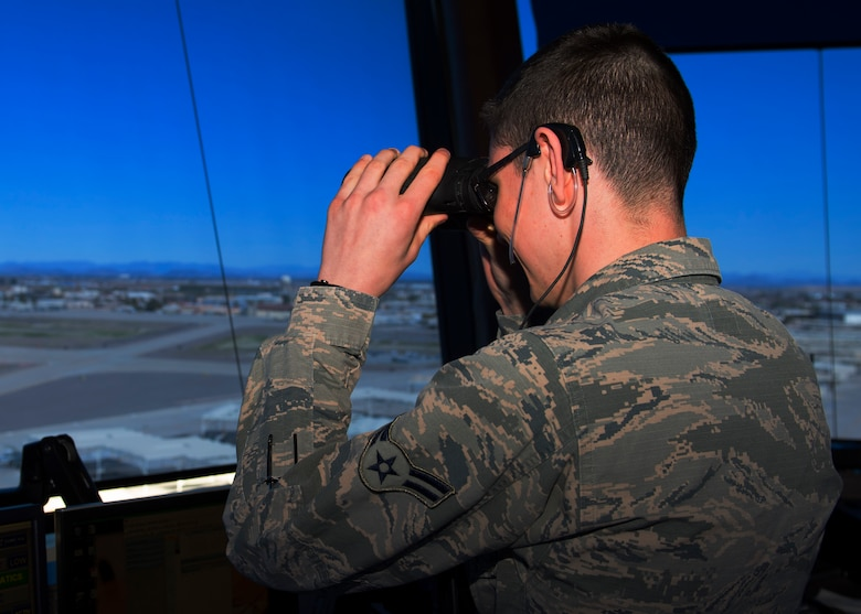 Airman 1st Class Morgan Ray, 56th Operations Support Squadron air traffic control apprentice, scans the flight line with binoculars at Luke Air Force Base, Ariz., Feb. 7, 2019.