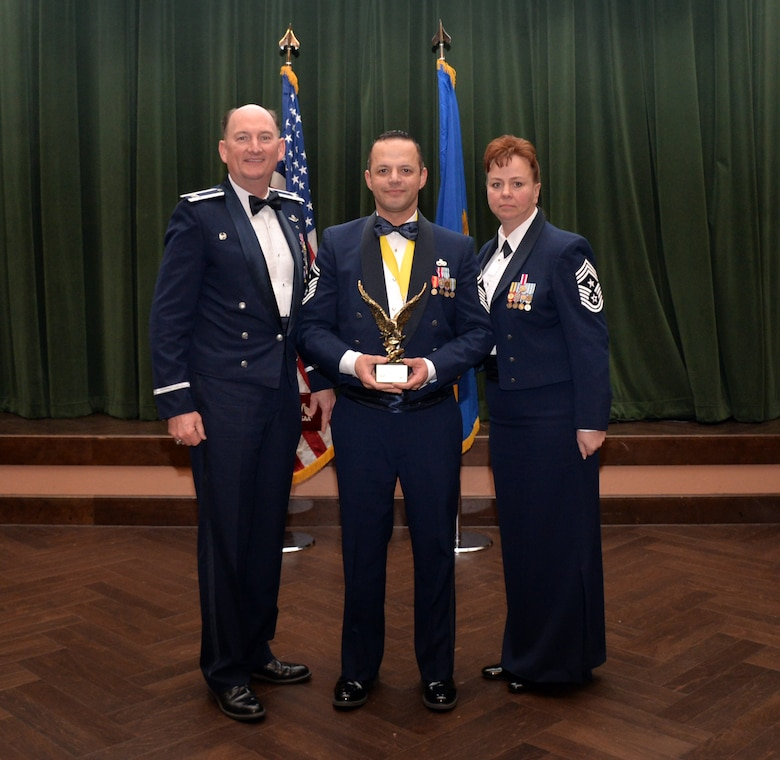 Col. Thomas K. Smith, 433rd Airlift Wing commander, and 433rd AW Command Chief Master Sgt. Shana C. Cullum, award Senior Master Sgt. Arturo Loya, 74th Aerial Port Squadron, as the First Sergeant of the Year at the 433rd AW annual awards banquet at Joint Base San Antonio-Lackland, Texas Feb. 9, 2019.